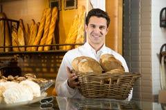 Équipez vendre la pâtisserie et les baguettes fraîches dans la boulangerie locale photos libres de droits