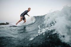 Équipez wakesurfing sur le conseil en bas de l'eau bleue contre le CCB photographie stock