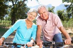 Équitation aînée de couples par la campagne Photo libre de droits