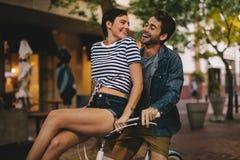 Équitation affectueuse de couples sur le vélo dans la ville Photos stock