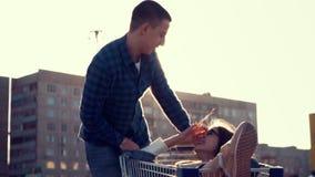 Équitation aimante de couples sur le parking ensoleillé du magasin dans le chariot d'épicerie, souriant à l'un l'autre banque de vidéos