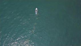 Équitation d'homme sur de support le panneau de palette sur des vagues de mer aux vacances d'été Silhouette d'homme se recroquevi clips vidéos