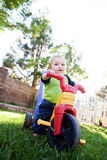 Équitation de bébé sur un jouet photos stock