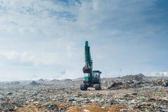 Équitation de bouteur à la décharge de déchets complètement de la fumée, des ordures, des bouteilles en plastique, des déchets et photos stock