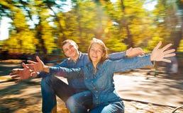 Équitation de couples sur le rond point en parc Image stock