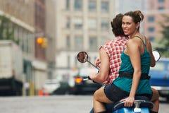 Équitation de couples sur le vélomoteur dans la rue Image stock