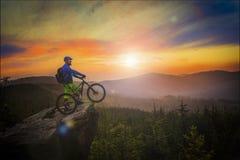Équitation de cycliste de montagne au coucher du soleil sur le vélo en montagnes d'été antérieures images stock