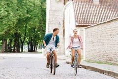 Équitation de déplacement heureuse de couples sur des bicyclettes Photo stock