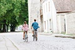 Équitation de déplacement heureuse de couples sur des bicyclettes Photos libres de droits