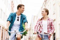 Équitation de déplacement heureuse de couples sur des bicyclettes Image libre de droits