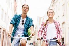 Équitation de déplacement heureuse de couples sur des bicyclettes Image stock