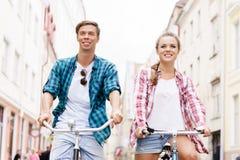 Équitation de déplacement heureuse de couples sur des bicyclettes Photographie stock libre de droits