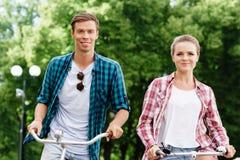 Équitation de déplacement heureuse de couples sur des bicyclettes Photos stock