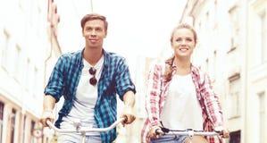Équitation de déplacement heureuse de couples sur des bicyclettes Ami et girlfri Image stock