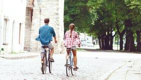 Équitation de déplacement heureuse de couples sur des bicyclettes Ami et girlfri Photo stock