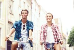 Équitation de déplacement heureuse de couples sur des bicyclettes Ami et girlfri Photographie stock
