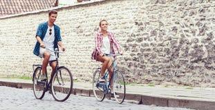 Équitation de déplacement heureuse de couples sur des bicyclettes Ami et girlfri Photographie stock libre de droits