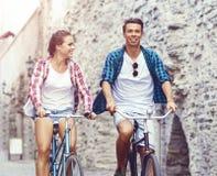 Équitation de déplacement heureuse de couples sur des bicyclettes Ami et girlfri Image libre de droits