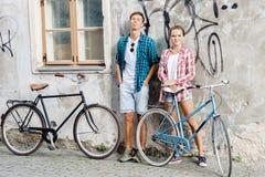 Équitation de déplacement heureuse de couples sur des bicyclettes Ami et girlfri Photos stock