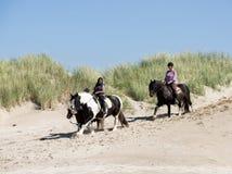 Équitation de deux filles sur un cheval sur la plage Photographie stock libre de droits