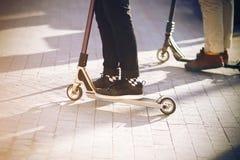 ?quitation de deux personnes sur des scooters sur le trottoir photo stock