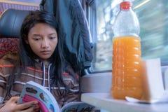 Équitation de femme par le guide ferroviaire et lu de voyageur photographie stock libre de droits