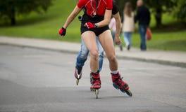 Équitation de femme sur des patins de rouleau au parc extérieur de patin images libres de droits
