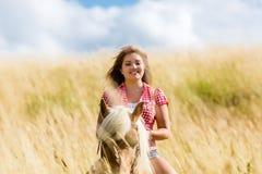 Équitation de femme sur le cheval dans le pré d'été Photo libre de droits