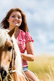 Équitation de femme sur le cheval dans le pré d'été Photographie stock