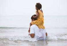 Équitation de fille d'enfant sur l'épaule du ` s de père et jouer en mer Photo libre de droits