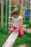 Équitation de fille sur une oscillation dans le terrain de jeu Image libre de droits