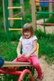 Équitation de fille sur une oscillation dans le terrain de jeu Photographie stock libre de droits