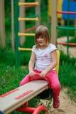 Équitation de fille sur une oscillation dans le terrain de jeu Images libres de droits