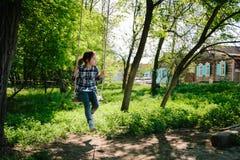 Équitation de fille sur une oscillation dans le village Photographie stock libre de droits