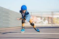 Équitation de garçon sur des patins de rouleau au parc extérieur de patin Images libres de droits