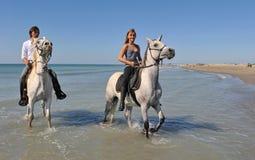 Équitation de Horseback sur la plage Photo stock