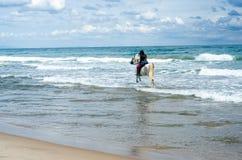 Équitation de jeune femme le long de la plage chez son cheval blanc photos stock