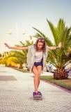 Équitation de jeune fille dans une planche à roulettes dehors Images libres de droits