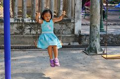 Équitation de jeune fille sur une oscillation en parc public photographie stock libre de droits