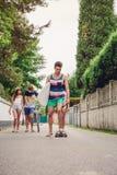 Équitation de jeune homme sur le patin et la planche de surf de participation Photographie stock