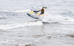 Équitation de jeune homme sur le ski de jet sur les vagues image libre de droits