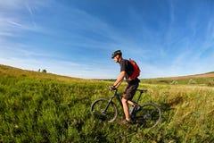 Équitation de jeune homme sur une bicyclette sur le pré vert avec un sac à dos image libre de droits