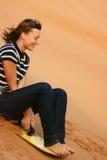 Équitation de l'adolescence de fille sur le sandboard de dunes de sable Images libres de droits