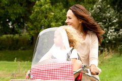 Équitation de mère et de fille sur la bicyclette en parc Photo stock