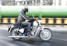 Équitation de motocycliste par la zone industrielle Image stock