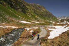 Équitation de Mountainbikers dans les Alpes Photographie stock libre de droits