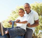 Équitation de père et de fils sur la balançoir en stationnement Images libres de droits