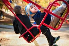Équitation de petit garçon sur une oscillation Photographie stock