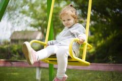 ?quitation de petite fille sur une oscillation et ondulation de ses jambes image stock