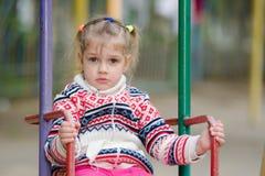 Équitation de quatre ans bouleversée de fille sur une oscillation Photos stock